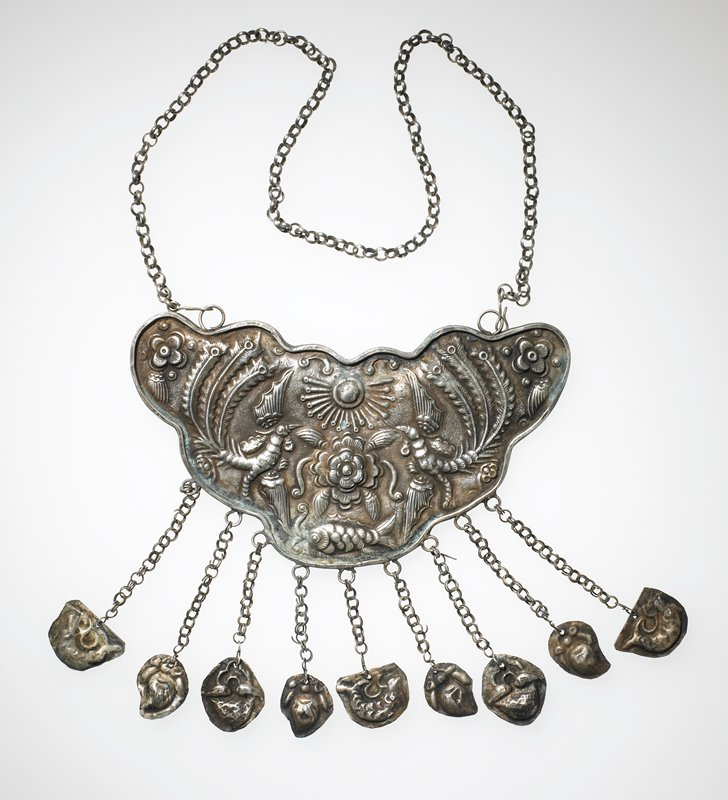 butterfly-shape pendant with nine attached small pendants; relief designs in large pendant include center floral motif with sun-like object above and fish below, phoenix on either side; floral motif at corners; small pendant motifs include central dragon and fish on either end