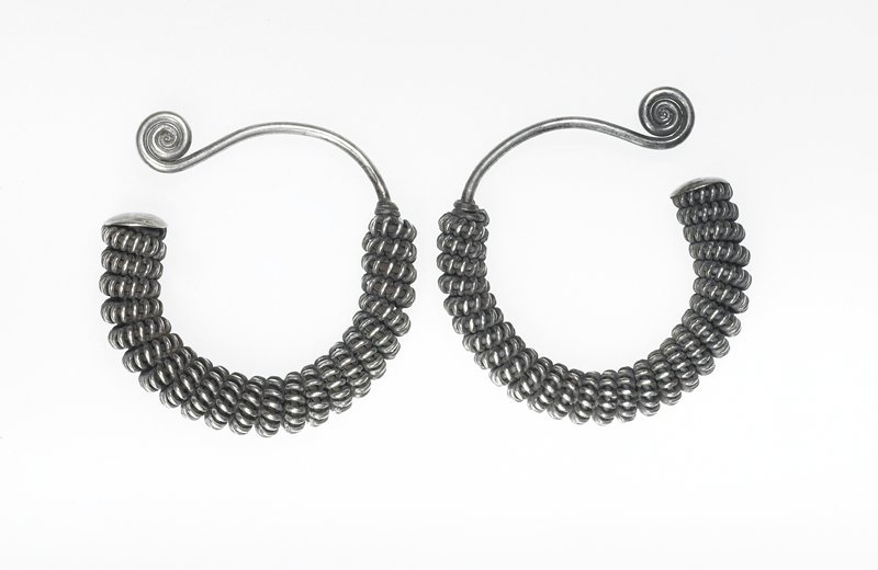 pair of earrings; each earring made from thick wire circle with curlicue on one end and flat piece on other end; main body is wrapped with coiled wire