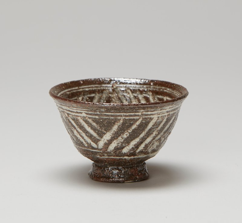 rather tall foot ring, slightly tapering inward at top; rounded bowl shape with outward-flaring rim; incised white designs on bronw--band of diagonal lines on exterior--flower shapes at interior bottom and diagonal lines at interior sides, from a two-piece set