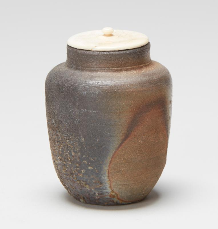 tea caddy; grey, brown and tan mottled glaze with rough textured areas; some green spots at interior; ivory cover with gold leaf on underside; inner silk brocade storage bag included