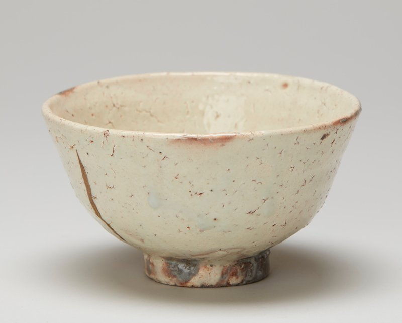 tea bowl; ring foot; rounded body with slightly outward-flaring sides; milky white glaze with grey areas around foot and vertical gold stripe on interior and exterior