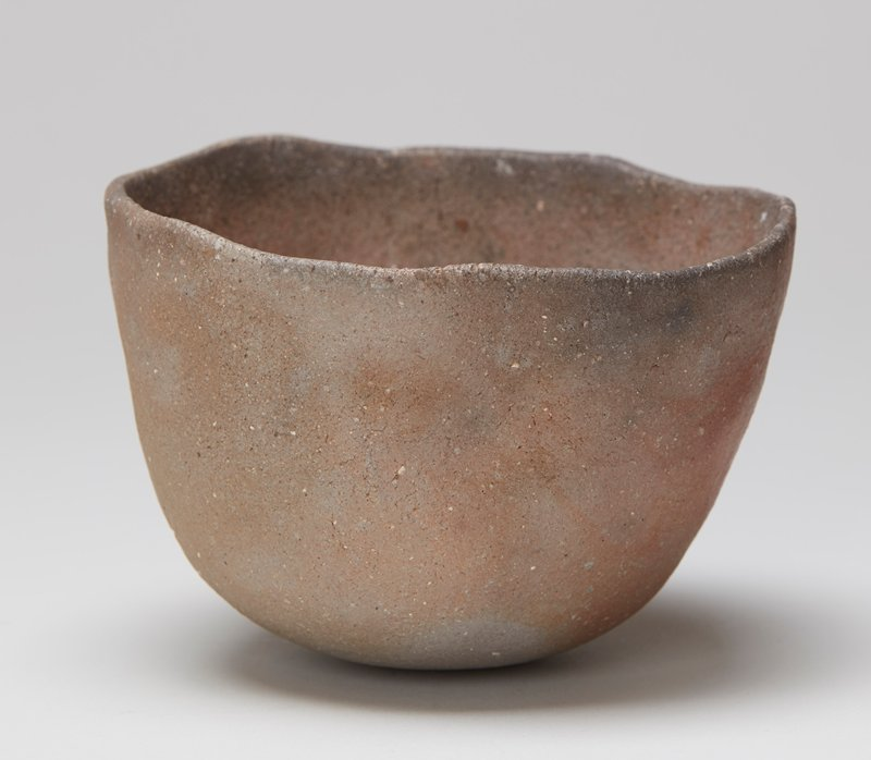 tea bowl made from a sand mold; rounded form with rounded bottom; slightly outward-flaring sides; grey, tan and golden brown