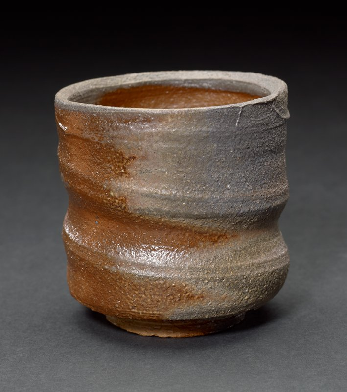 ring foot; cup shaped with straight sides; incised ribs on exterior--irregular; swirl at interior bottom; brown, grey, tan