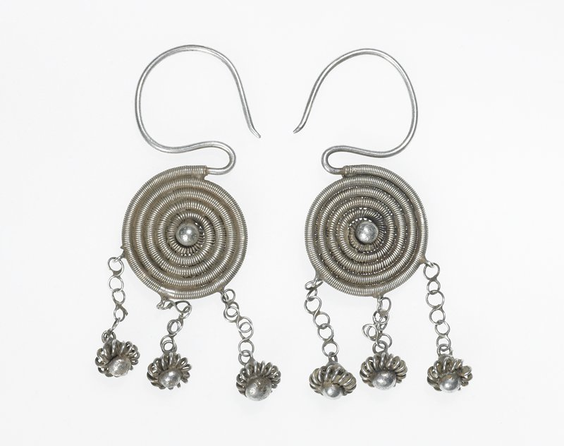 pair of earrings; each main body is a circular disk of coiled wire; disk has sphere at the very center on both sides; three chains with pedestaled flowers dangle from the bottom; earpiece is a curved and sharpened wire