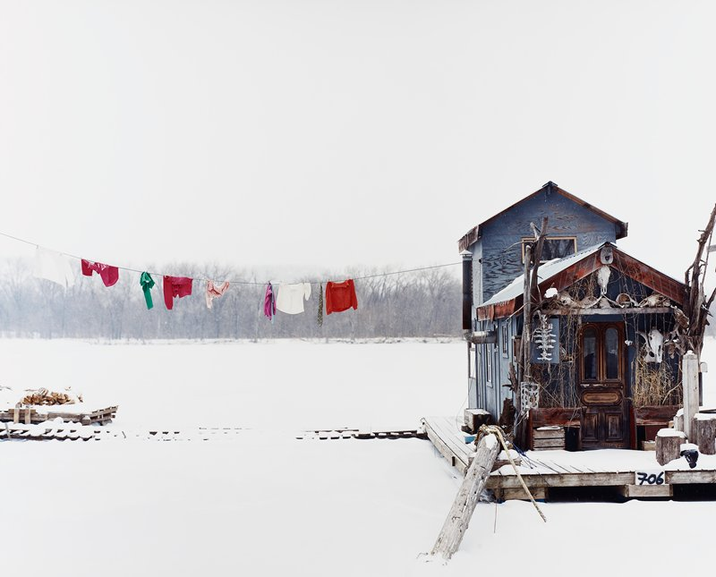 tiny blue house with platform (dock?) around it; many skulls and animal bones above and around door; snowy; clothes on clothesline at left