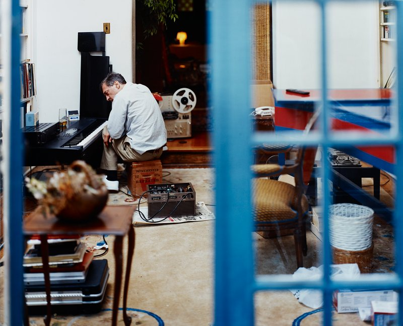 man wearing blue striped shirt sitting on ammo box looking at electronic keyboard; reel-to-reel tape players; blue framed door with glass panels at edges of image