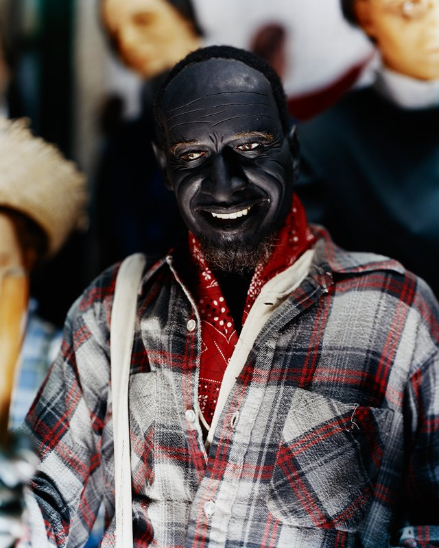 wax figure of a dark-skinned man, smiling, wearing plaid shirt and red neck bandana