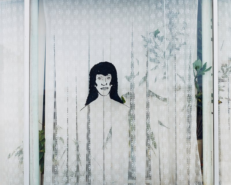 long lace curtains; center panel has woman's face painted on it in black; leafy plants behind curtain