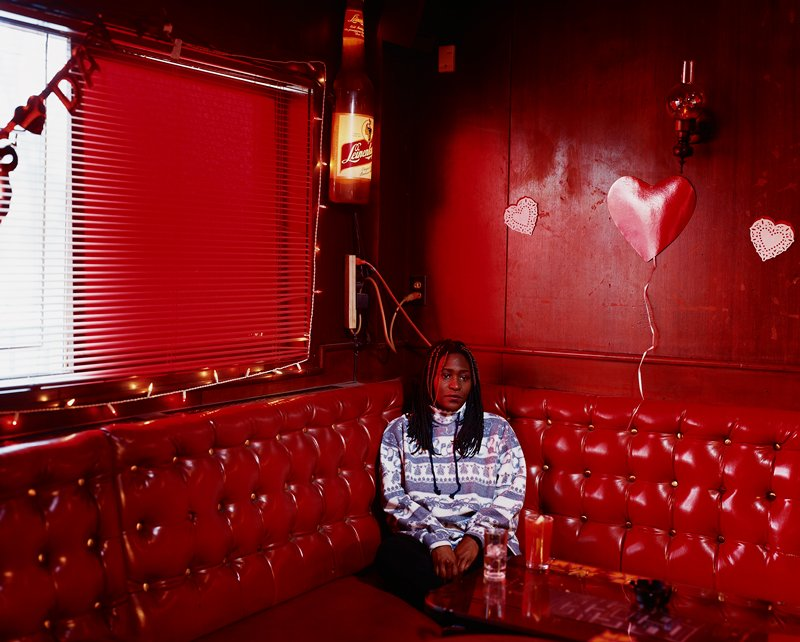 black woman seated in a red leather banquette behind table; red wall; three heart decorations on wall; Leinenkugel's beer bottle light on wall