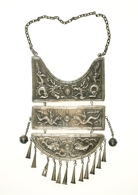 three-section pendant necklace; hollow; motifs in relief; top section has two open-mouth dragons with ball between; second-section rectangular has two lizard-like creatures being ridden by monkeys carrying sword-like implements; in center is double-fish motif with two additional small fish on top and bottom; lowest section has two large fish with a double-fish motif between and two smaller fish below; lowest section is semi-circular; two pendant balls attached to center section; 12 cone-shaped pendants attached to lower section