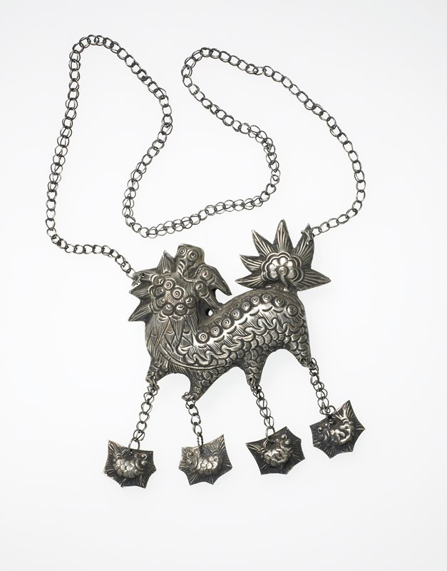 pendant necklace very similar to 2007.17.12; lion-like creature with flower motif tail; four pendant fish-like creatures suspended, one from each foot; designs in relief are the same on both sides of hollow pendant