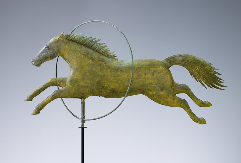 horse jumping through a hoop, at a 45° angle; horse's body, legs and head are three-dimensional; ears, tail and mane are flat; green and gold patina