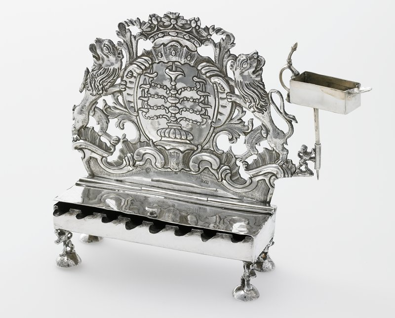 "back has openwork design with lions flanking a cartouche with a menorah; light incised lattice design on top of lamp compartment cover; tiny lions on domed feet; cover of lamp compartment detaches from the main lamp body when it is opened more than 75%, possibly due to the fact that it seems to be missing a hinge pin on the ""back left"" hinge."