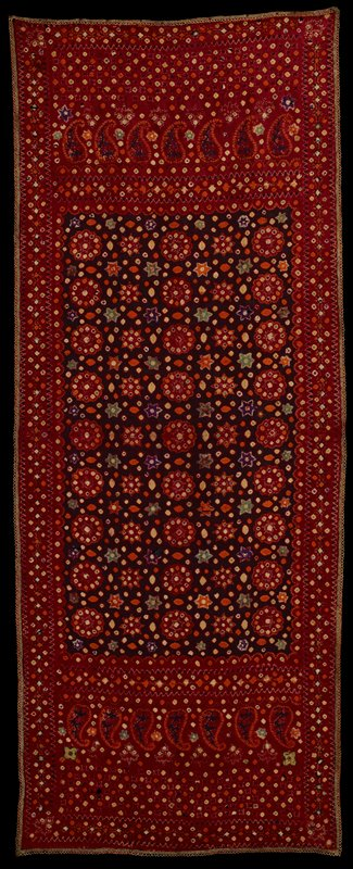 panel in predominately maroon and brown, edged in metallic gold crochet; central panel has maroon rondels with green central stars, edged in multicolored dots, orange, green and purple stars and multicolored spots and football shapes; purple repeating star patterns on long sides; paisley designs at ends