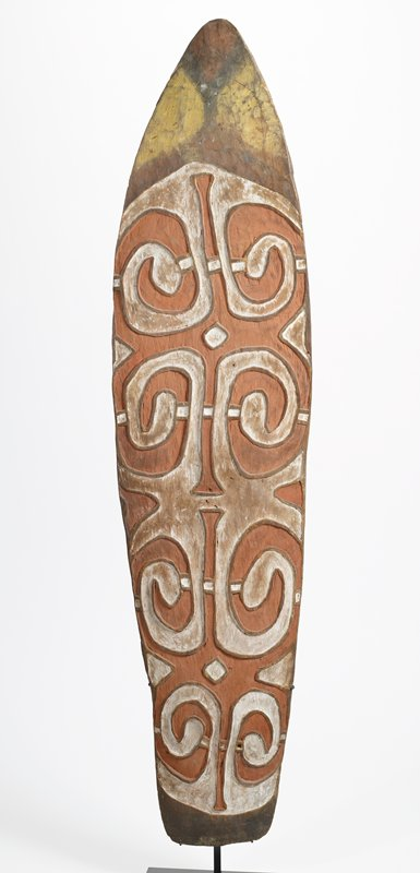 "roughly wedge-shaped, slightly curved, with pointed arched top; carved in relief and decorated with dark orange, white and yellow pigments and traces of black pigment; two relief designs on top of one another, each with four corner spiraling loops and two vertical ""legs""; handle on back"