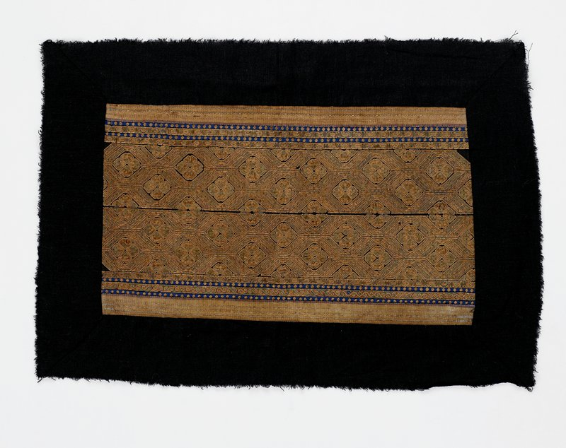 """panel with dark blue borders; central area embroidered with gold and pale green threads in square flower-like motifs surrounded by linear geometric patterns; border bands with gold dots on blue, scroll band, scroll and """"H""""-patterned band and striped bands"""