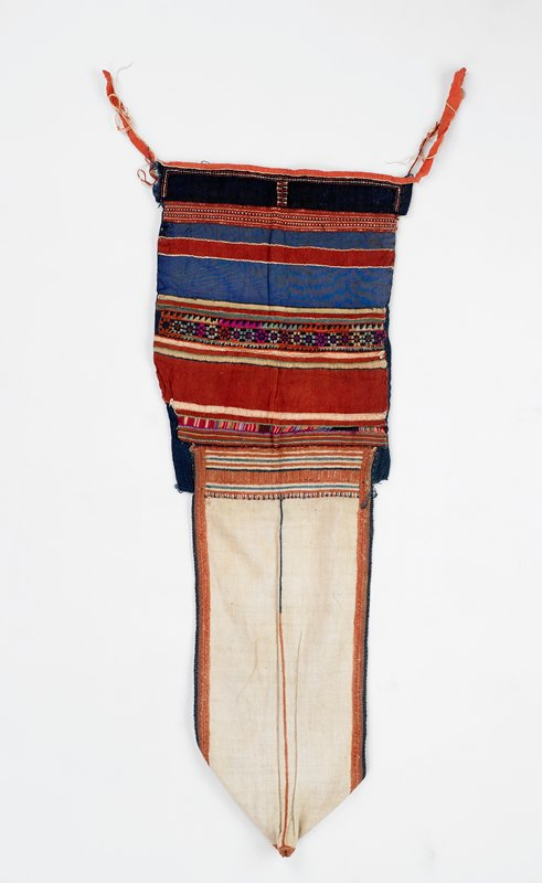 hood-like garment; cream woven fabric at one end with embroidered trim and edging in light brown and blue; blue fabric panel at opposite end with embroidered striped strips and band of cross stitch and appliqués of rust-colored fabric; ties at corners of blue panel