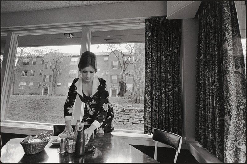 woman learning over table in foreground; two men in background looking at woman through window