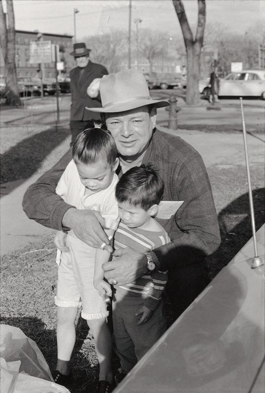 Man Wearing Hat Looking Into Camera Crouched Down With Arms Around Two Young Kids