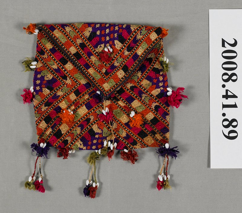 small embroidered bag with tassels and shells; embroidery covers almost entire surface of bag; colors include red, orange, yellow, green, tan and purple; shells attached to tassels located along edges and in center front and back of bag