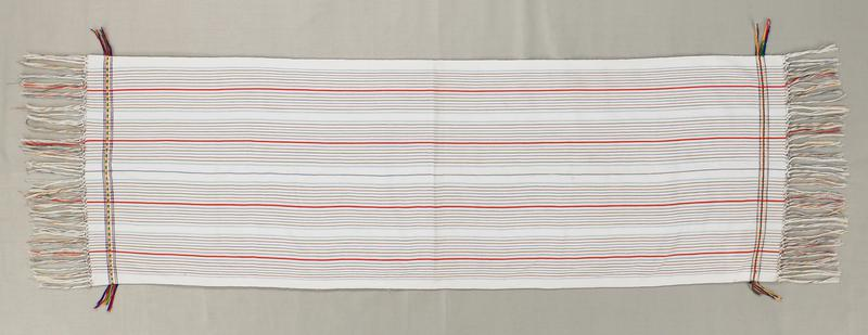 white shawl with blue, green, yellow, red and orange stripes lengthwise; borders at ends have five stripes; center stripe is either red/green or yellow/green; self fringe at both ends