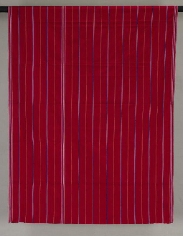 """red striped skirt; stripes primarily blue with thin yellow and white accents; 1"""" wide band of stripes along top and bottom edges; side edges unfinished"""