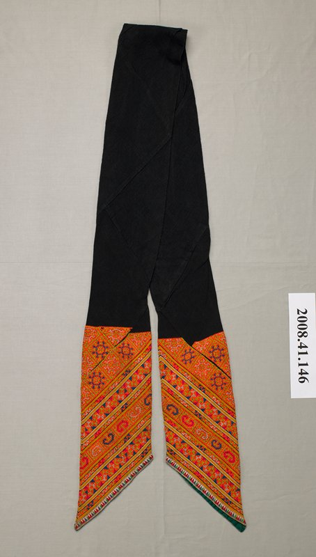 "black with embroidered bands approximately 15"" wide at pointed ends; orange, green, blue, red and white geometric motifs in bands; edges bound with print fabric on front and dark green plain fabric inside"