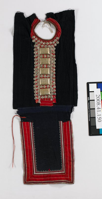 "woman's breast cover in two sections; top is black with red fabric at front and neckline; metal stars and 15 oblong metal plaques cover center front; lower section is blue with approximately 3"" wide band of applied fabric and embroidery at sides and bottom in red, white, blue and green"