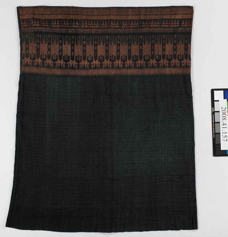 tube skirt; blue top section with subtle dark orange horizontal threads interwoven; bottom black band woven with pairs of stylized quadrupeds in brown with diamond-shaped heads; geometric zigzag and diamond motifs above and below quadruped band; grey, rust and golden brown designs