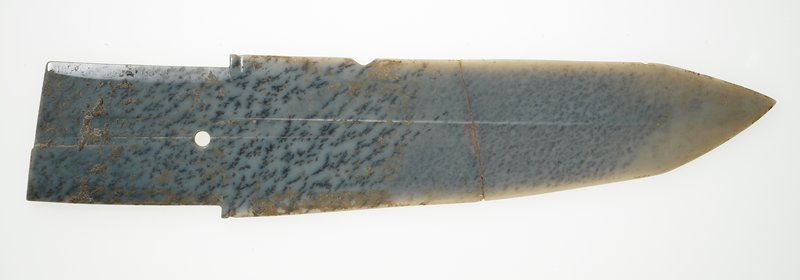 grey jade spotted with black-moss veins; traces of earthlike substance. No surface decoration. Restoration near center of blade.