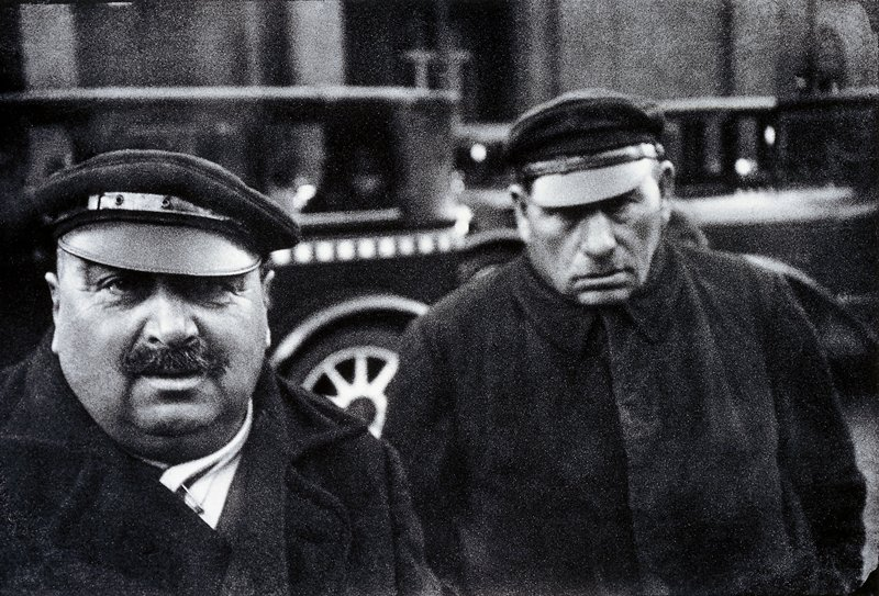 close up of two men wearing hats and overcoats; the larger man has a mustache