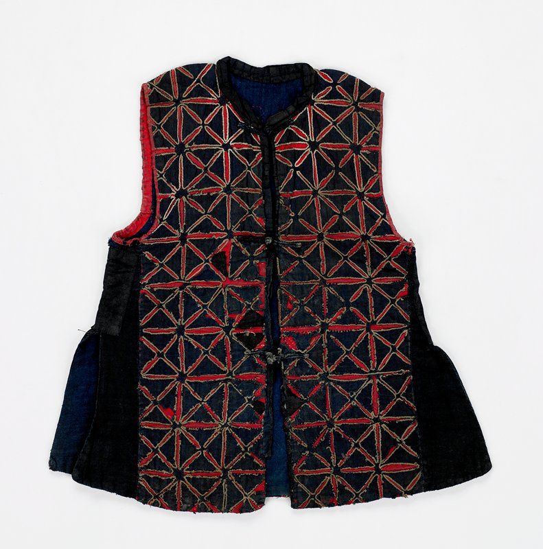 black with three frog closures; red and tan applique forms in X shapes within boxes; blue lining