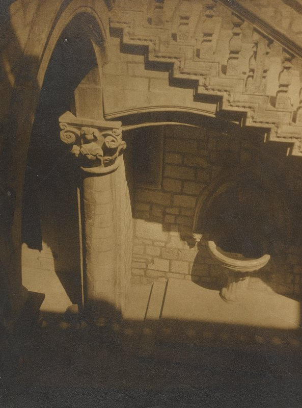 sepia tone; view from above of staircase at top with column at left; font at bottom right; shadows