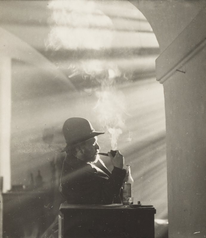 profile of seated man smoking pipe and wearing hat