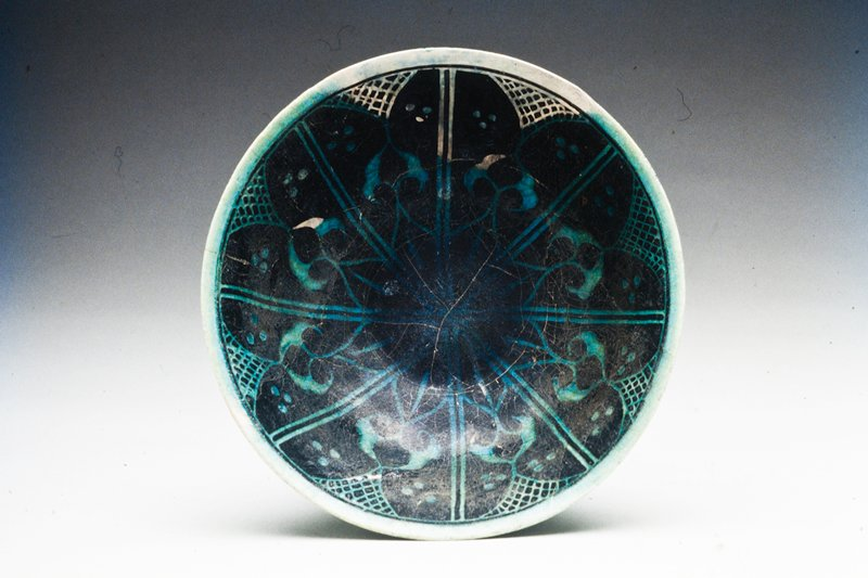 Bowl, black. Champleve design under blue glaze.; eight part design of leaf form with cross-hatching between leaf at rim.