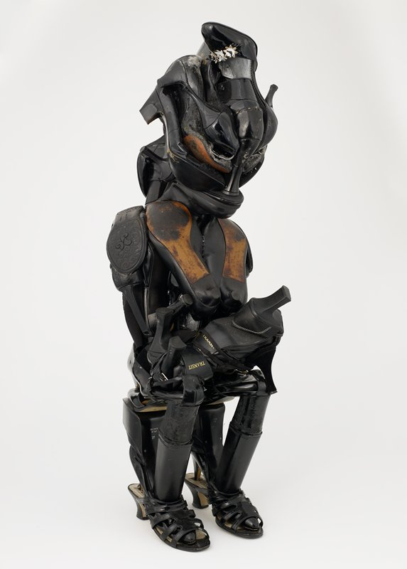 sculpture in the form of an abstracted woman holding a baby on her lap; made of various types of black ladies' and girls' shoes; topmost shoe has white and gold flowers on upper