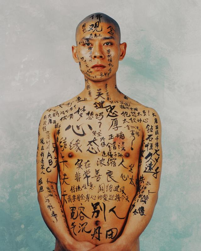 head, torso and arms of a man with Chinese characters written in black on his face, arms and body