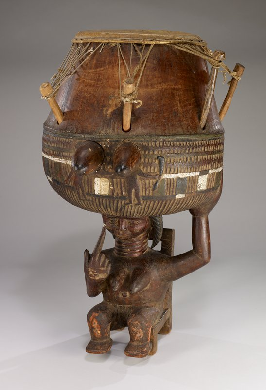 base of drum is three-dimensional sculpture of a nude woman seated on a low chair with a ladder back, with her hair in three braids, holding drum body on her head and with her PL hand; PR index finger on PR cheek; body of drum is rounded at bottom with incised geometric bands and two human figures at front; skin head stretched with strings on wooden pegs; white, green and black pigments