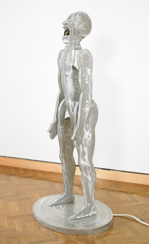 "standing abstracted man with flat legs, arms and toso; flat head (profile) with mechanized hinged jaw and speaker inside mouth; brushed silver patina; silver box attached with cords houses separate Kenwood compact disc player with remote control; CD included: ""Four Gods"" by Jonathan Borofsky"