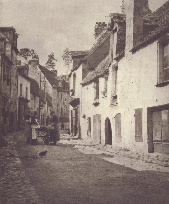 narrow street with people surrounding a cart, cat looking back at them; matted