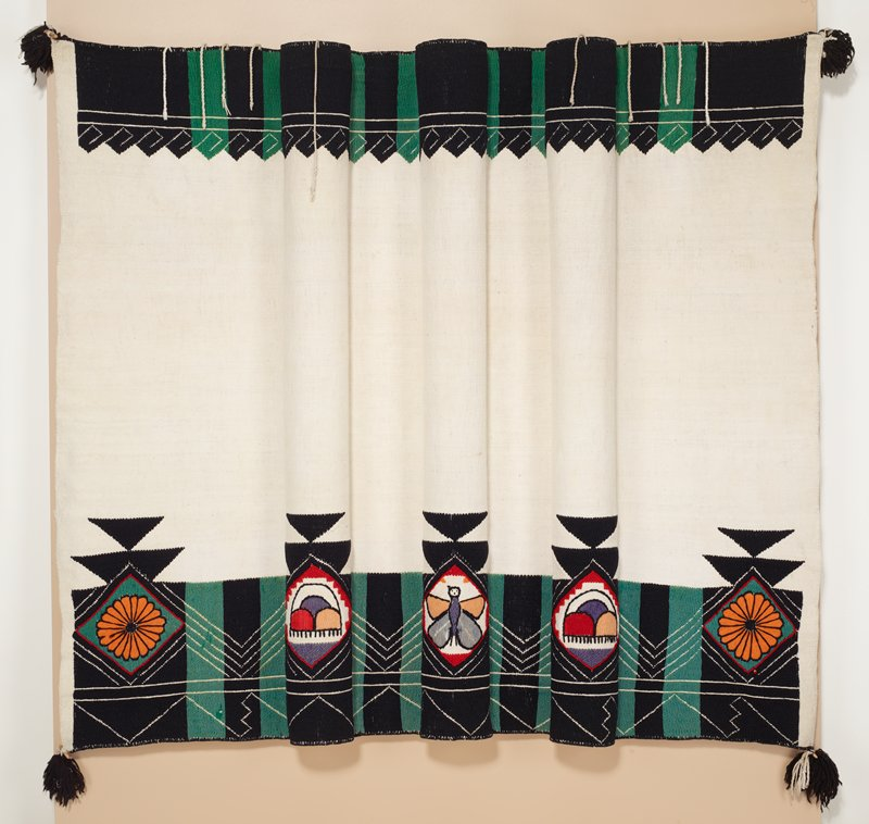 """Rectangular textile with green and black bands of embroidered decoration along top edge on non-dyed, woven, plain weave. Similar bands of green and black embroidered pattern along bottom edge with five multi colored embroidered images: orange flowers at outer ends and a butterfly at center. Black tassels at each corner with 1"""" wooden piece tied into each."""