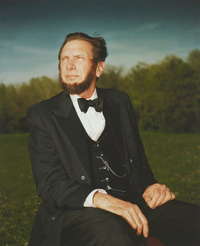 portrait of bearded man dressed as President Lincoln; man sits looking to PR with hands resting on thighs; silver watch chain attached to vest; red, gold and silver belt buckle slightly visible under vest; blurry line of trees and blue sky in distance; framed behind glass in black wood frame; one of a set of 18 photographs to be displayed together