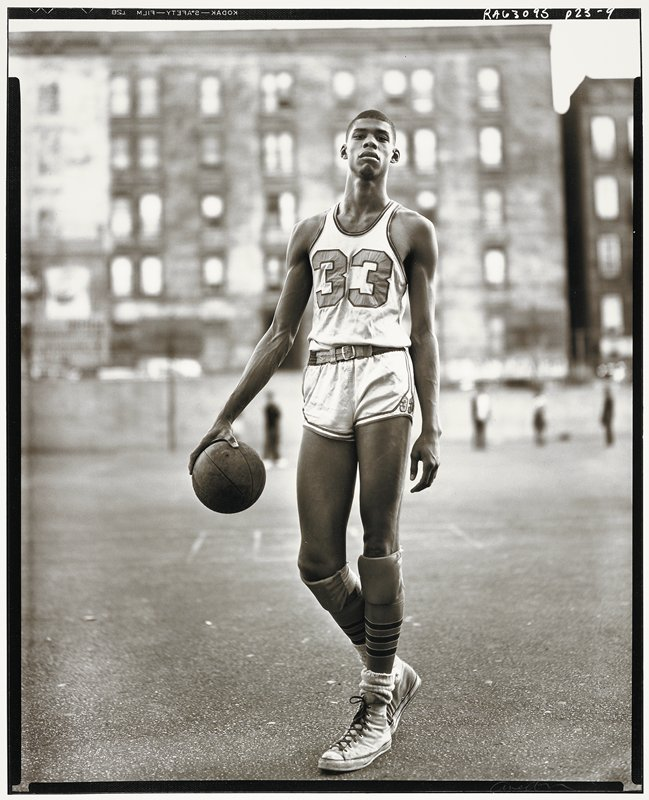 young black man wearing a basketball uniform with the number 33, holding a basketball in his PR hand; tall city apartment buildings in background