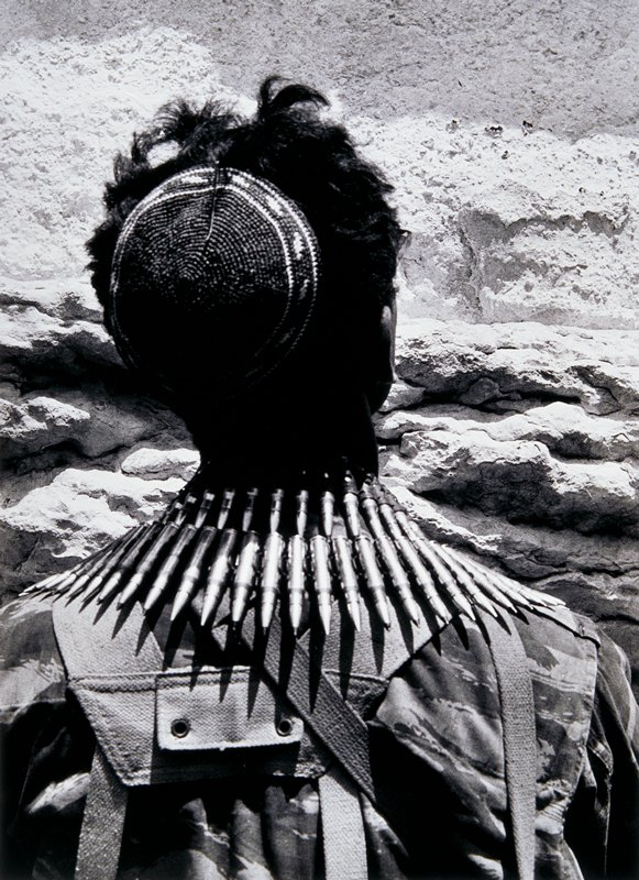 head and shoulders of a soldier seen from the back, facing a wall; wearing a yarmulke, 2 rows of bullets around his neck and camoflaged shirt
