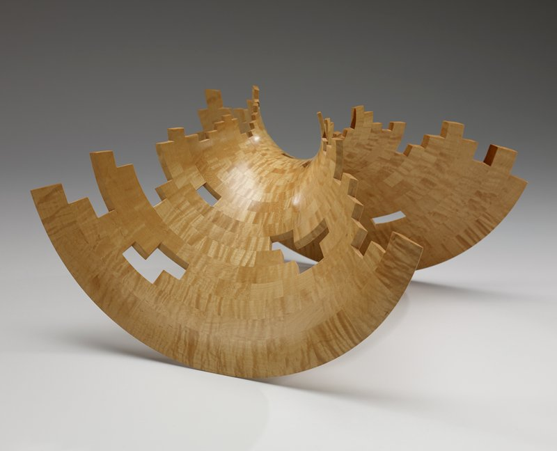 98-44; flat piece of wood that has been carved in two directions so it rests on two rounded edges and can rock; scattered open spaces in geometric shapes