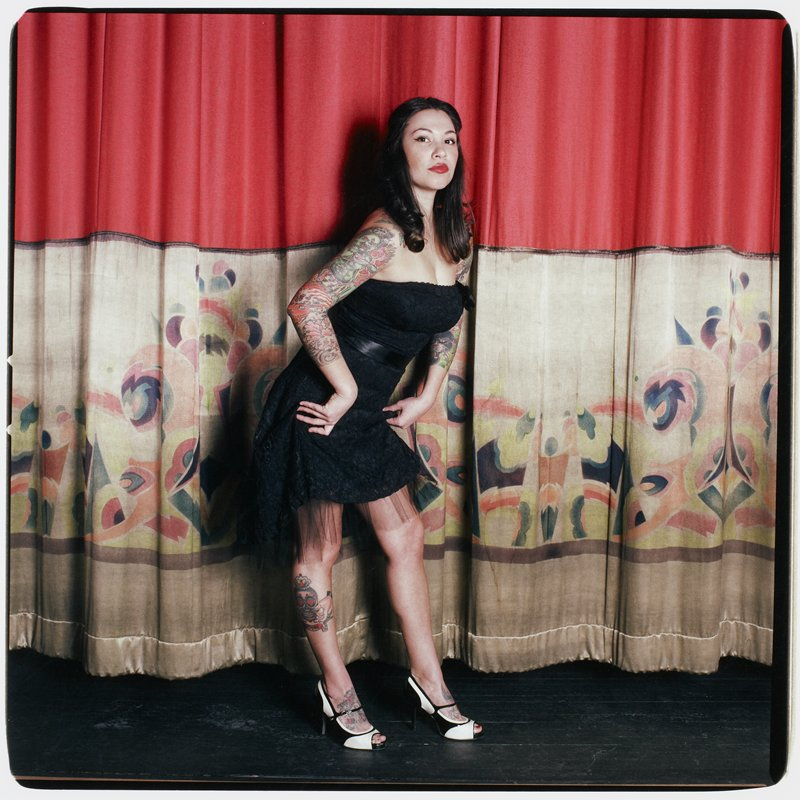 woman standing in front of a curtain (red on top, multicolored pastel stencils on cream on bottom); woman wears a strapless black dress and black and white shoes and has tattoos on her feet, PR leg and both arms. Album