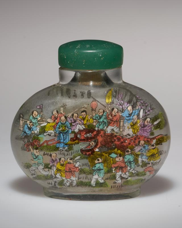 frosted clear glass with images on each side of children in brightly-colored garments, carrying lanterns and fans, playing drums and cymbals, and dancing with long dragon puppets; green glass (or jade?) stopper top