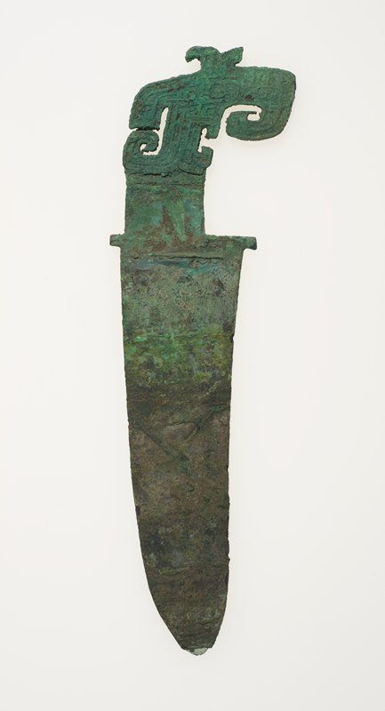 This weapon displays the assymetrically placed tang and the strongly beaked, crested head of a bird that was a ubiquitous motif in the bronze art of Yin-time. The details of the bird's head are in rather heavy thread relief. This piece is similar to Karlgren Number 81, plate 99, but is of bronze throughout. Patina green