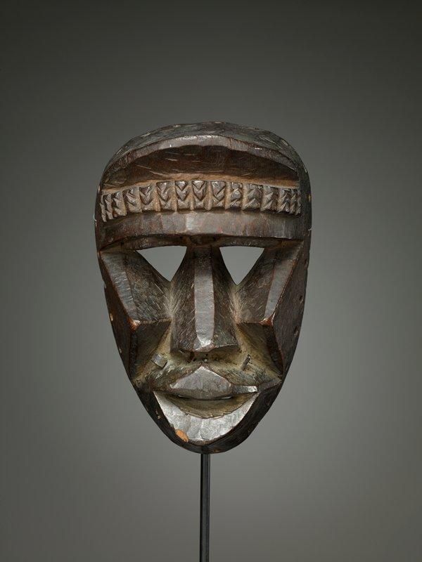 human face mask; stylized, geometric features; several metal elements (nails, etc.) on upper lip; triangular cheeks and nose; horizontal band of stylized braids on forehead; triangular eyes; thick lips