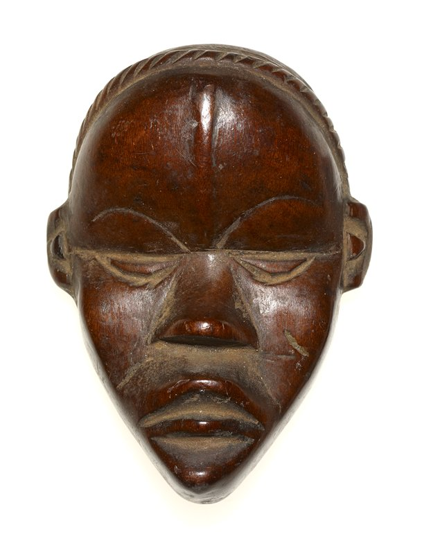 small human face; slightly concave, forming a slightly crescent-shaped profile; incised band around top of head from ear to ear; vertical line at center of forehead; closed, half-circle shaped eyes; wide, frowning lips; medium brown patina